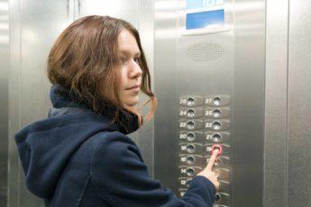 Young teen pushing elevator control