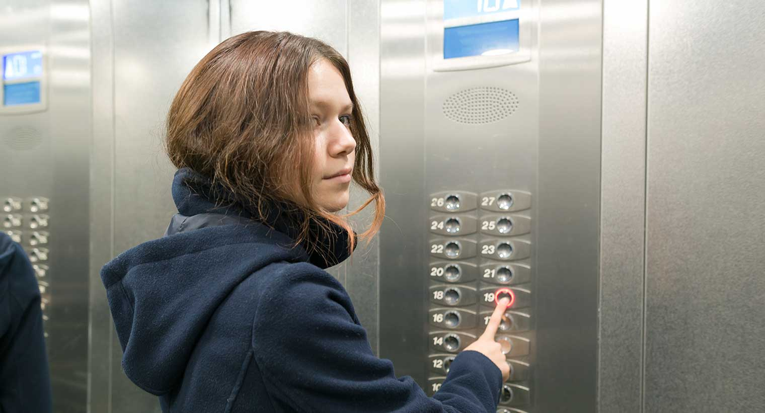 Young teen pushing elevator control